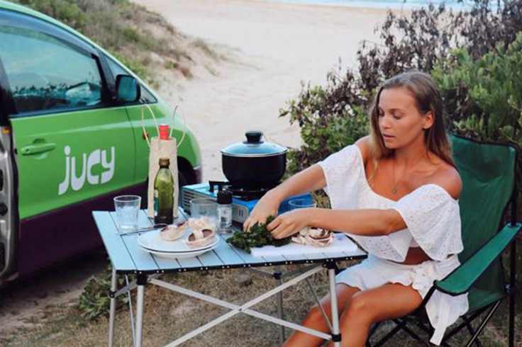 woman eating dinner next to a jucy campervan travelling in summer