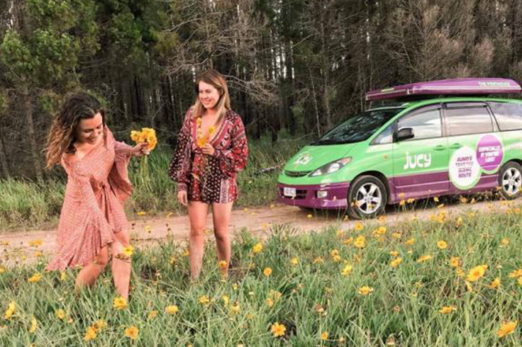 two girls pick spring flowers in a field in australia with a jucy campervan in the background