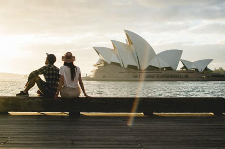couple sit in front of opera house