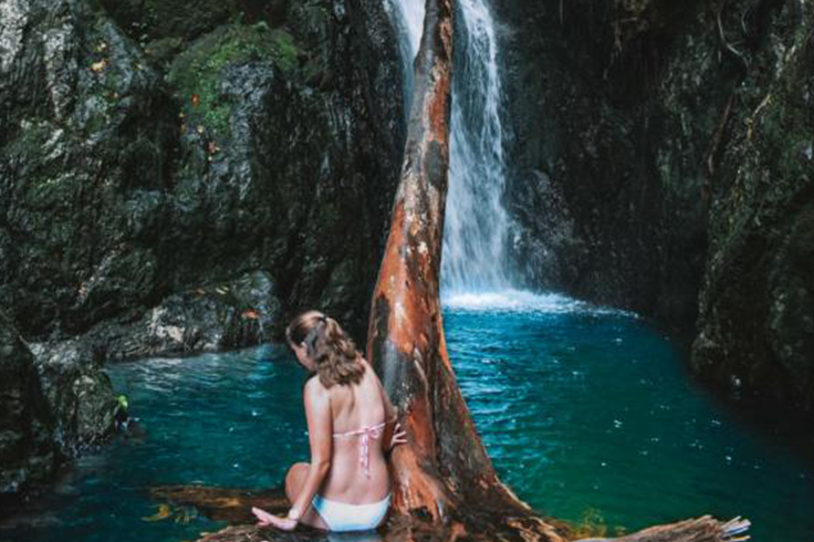 girl sits on a rock in front of fairy falls near cairns