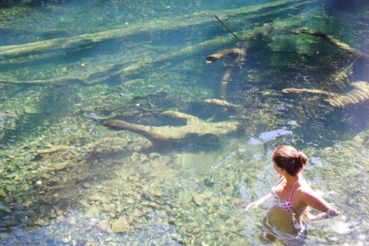 girl swims in pool in daintree rainforest