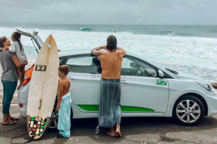 family stands by jucy car in byron bay australia