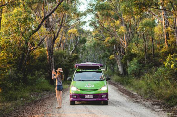 Girl taking photo on a tree lined road with a JUCY campervan