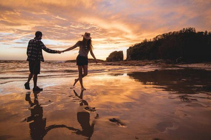 Couple walking along a beach at sunset