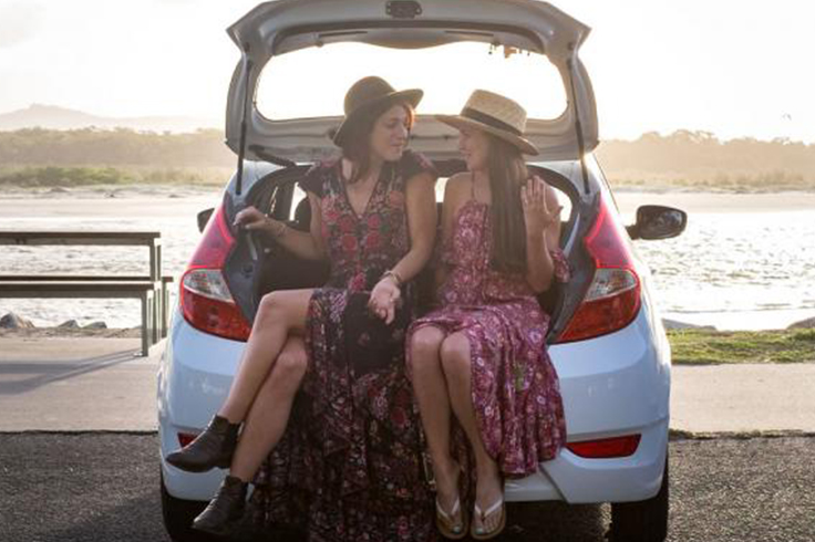 Two girls sitting in the back of a JUCY car at the beach