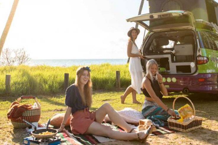 3 girls having a picnic and cooking with a JUCY campervan