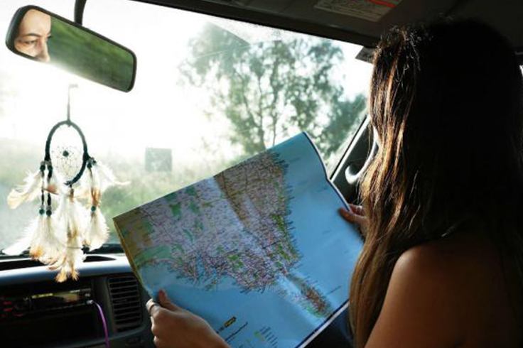 A girl looking at a map in a campervan
