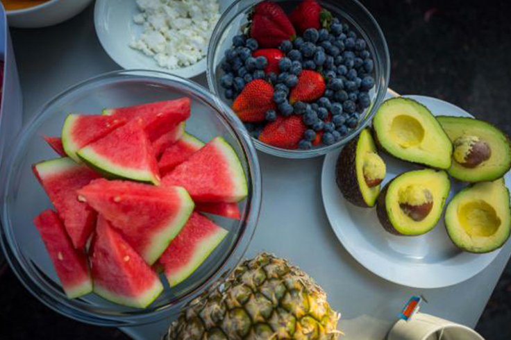 A selection of fruit and avocados on a camping table