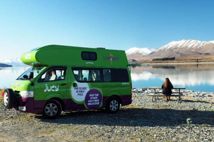woman sitting at a camping table next to campervan mountains and lake