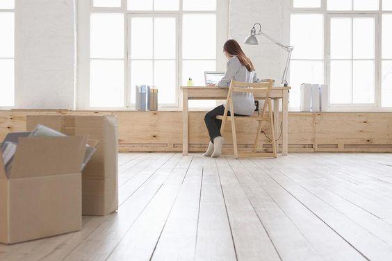 Demoiselle qui travaille à domicile sur son bureau en bois sur le bord de la fenêtre