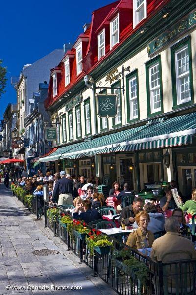 Terrasses de restaurant dondées de clientèle sur le bord d'une rue passante