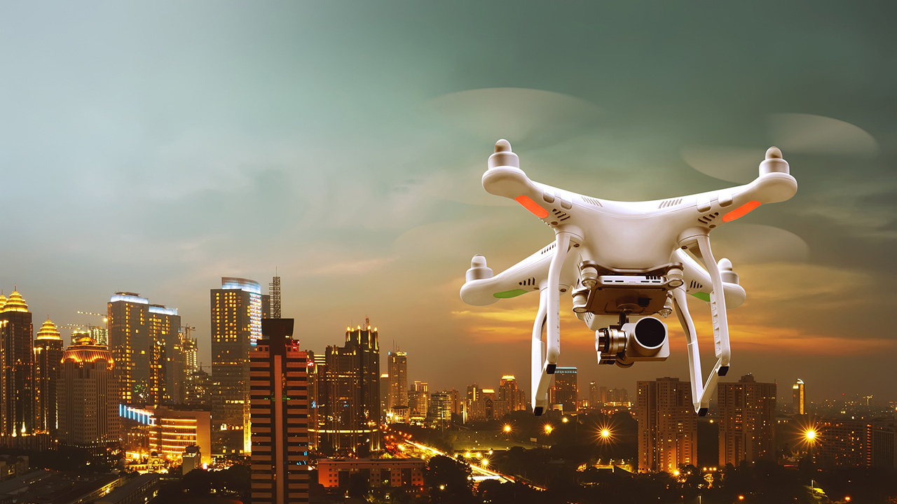Small white drone flying over the city