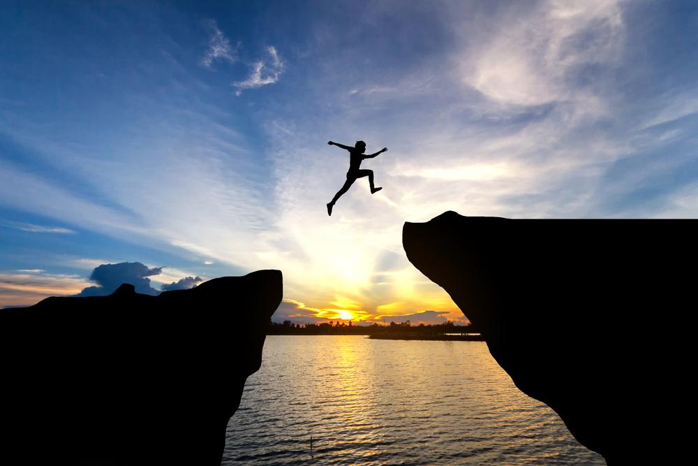 崖を飛び越える人