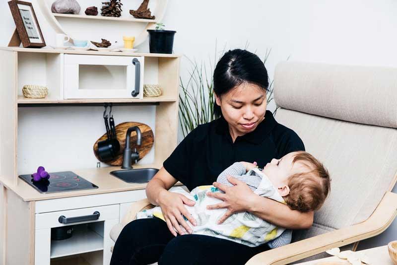 An Educator nurses a baby.