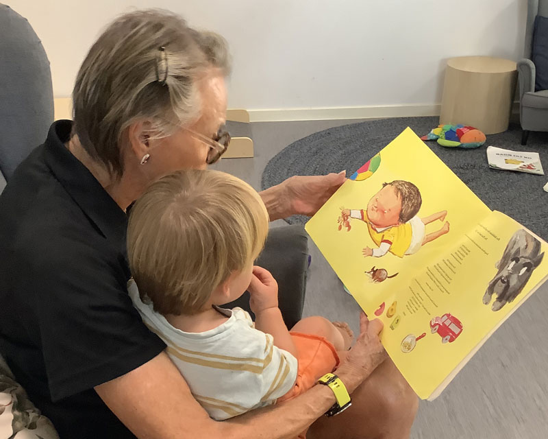 Educator working with multi-aged children reads a book to a child.