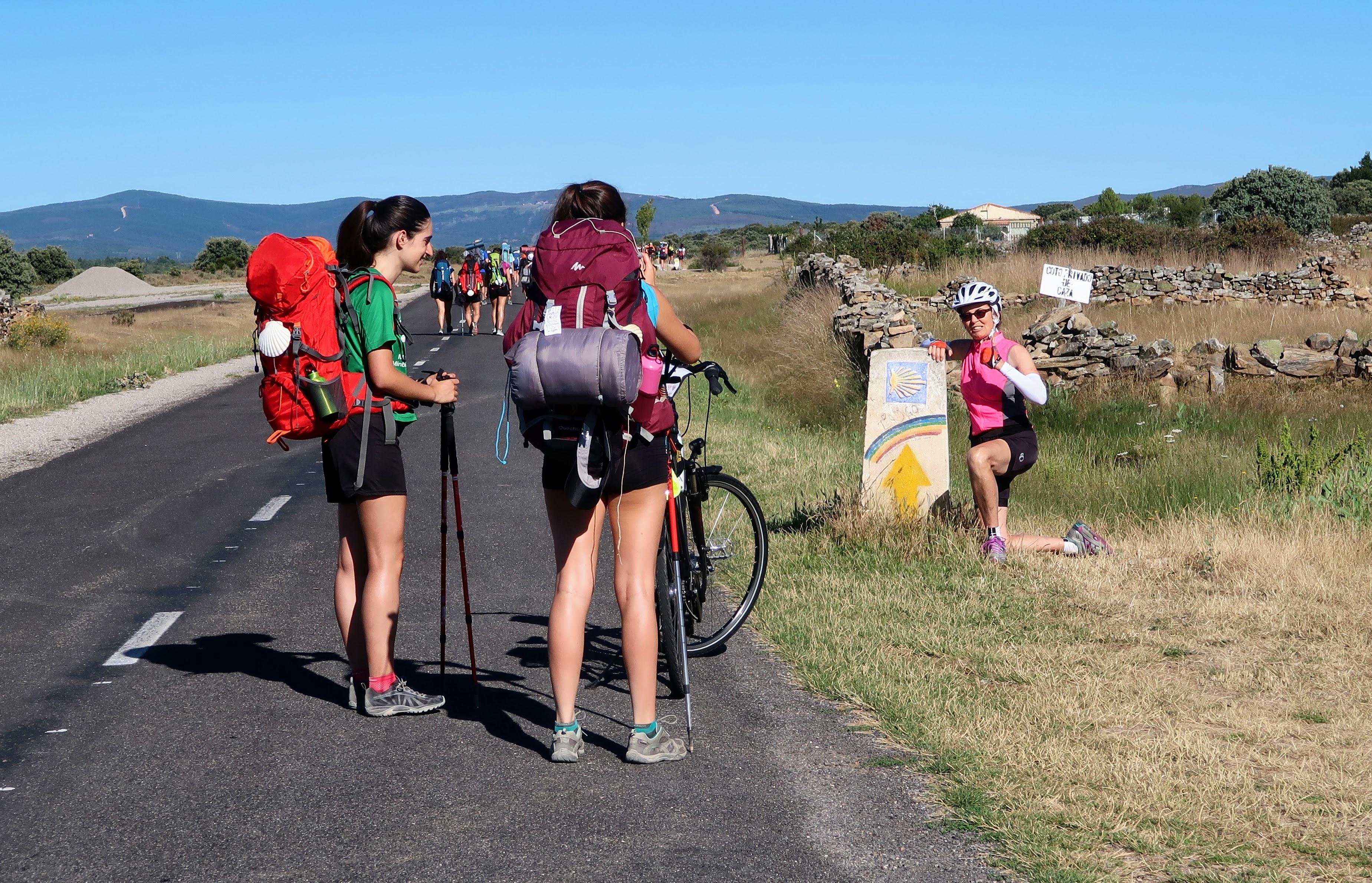 Camino cyclist with pilgrim walkers on Camino de Santiago