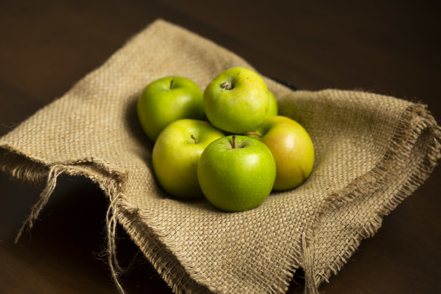Six apples sitting in a bowl covered with burlap.