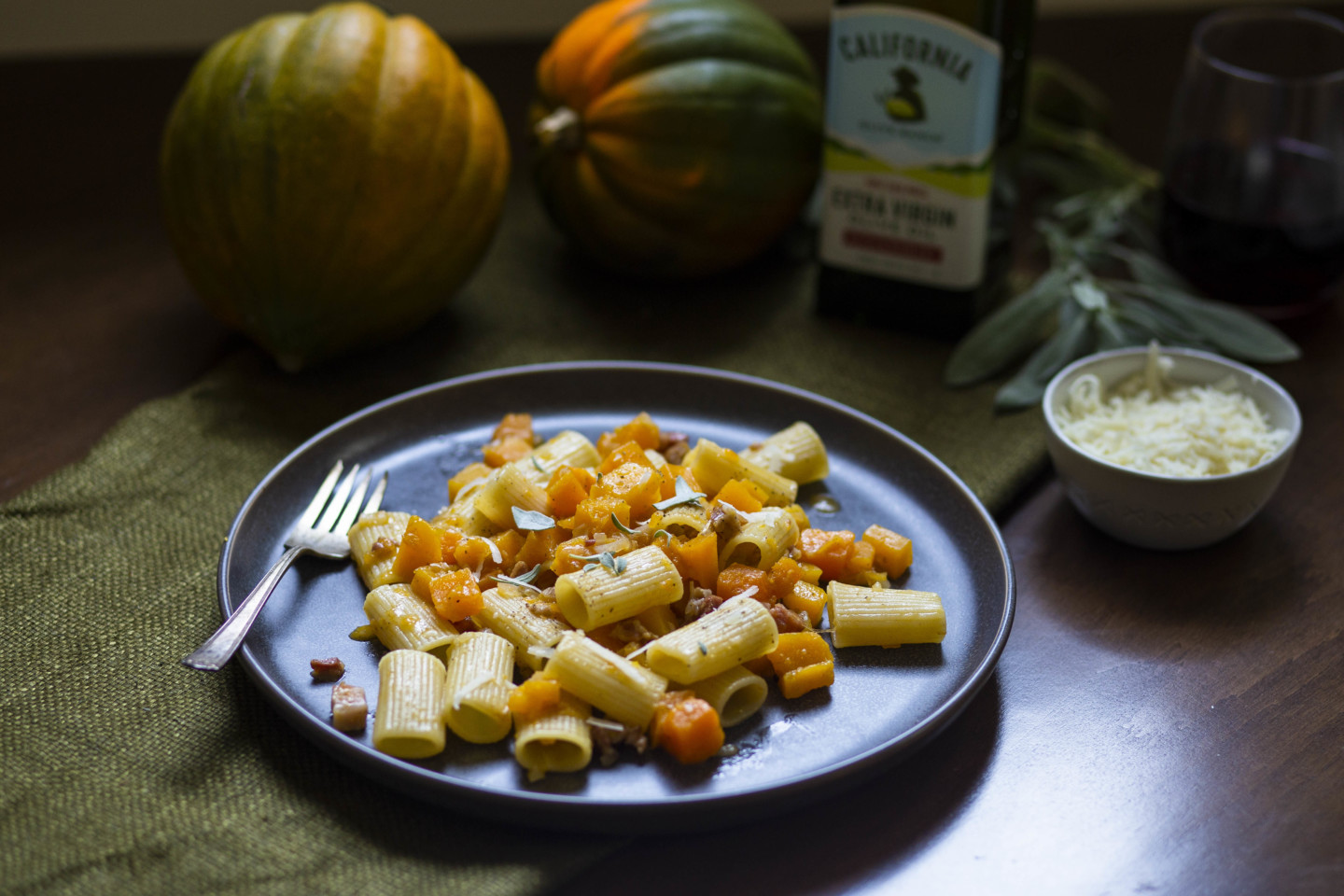 Rigatoni with Pancetta, Pumpkin, and Sage. In the background there are two squash, a bottle of extra virgin olive oil, sage, and parmesan cheese.
