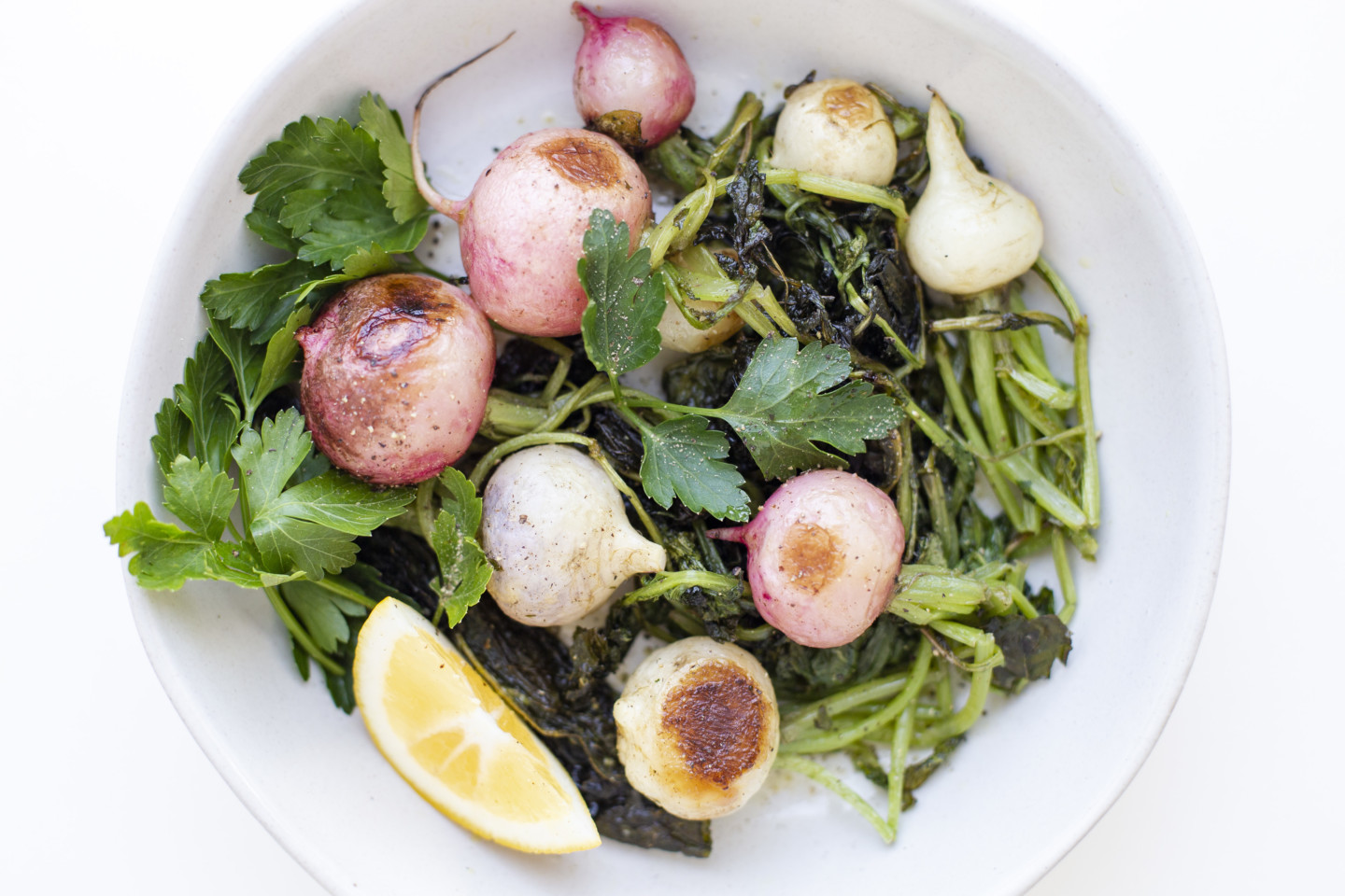 A plate of several roasted radishes, greens, and California Olive Ranch Everyday Extra Virgin Olive Oil.