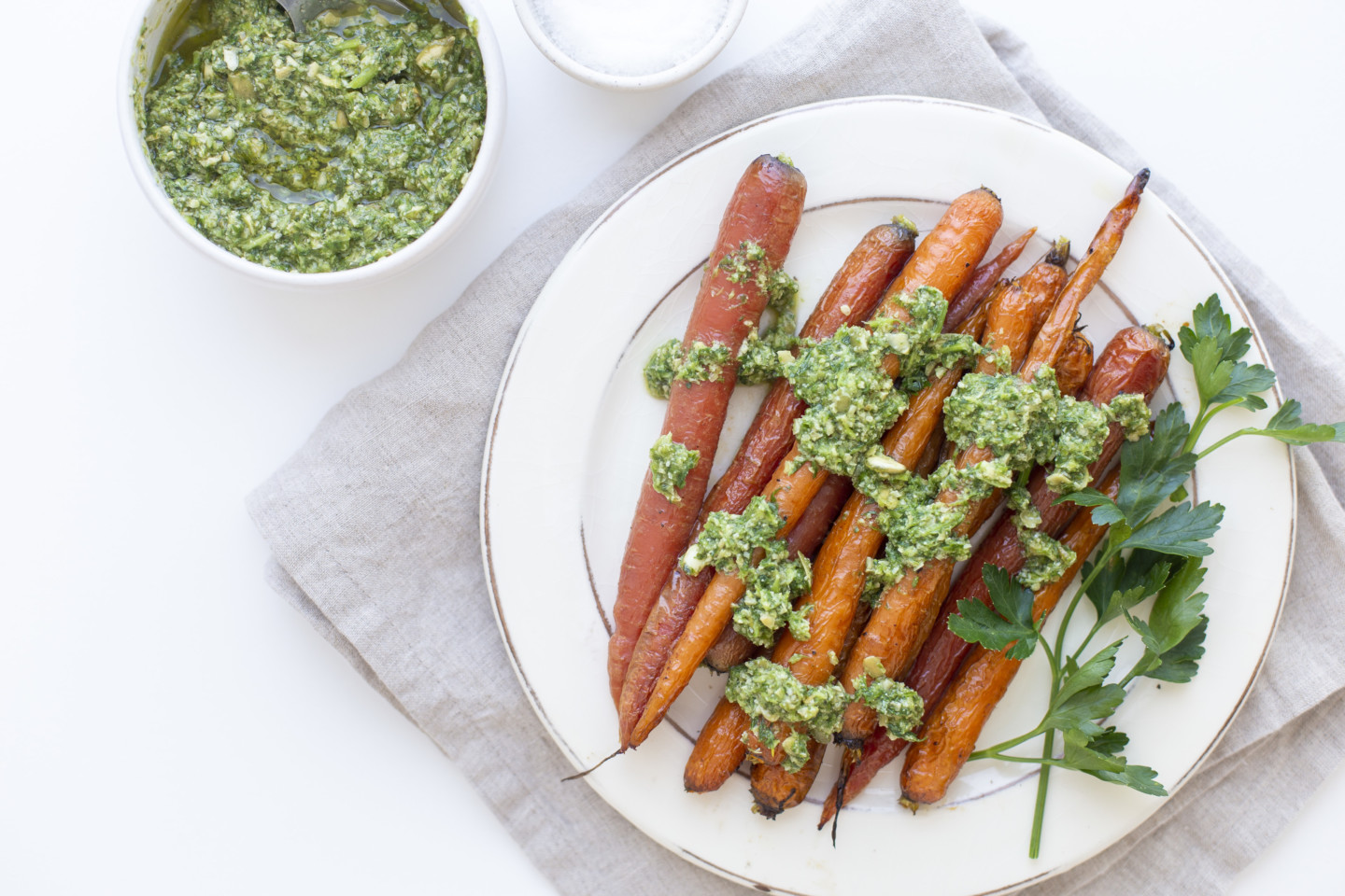 A plate of roasted carrots that are topped with carrot top pesto along with a smaller bowl of pesto.