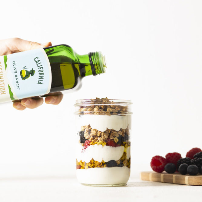A bottle of California Olive Ranch Everyday Olive Oil being poured into a jar of a yogurt parfait, complete with berries and granola.
