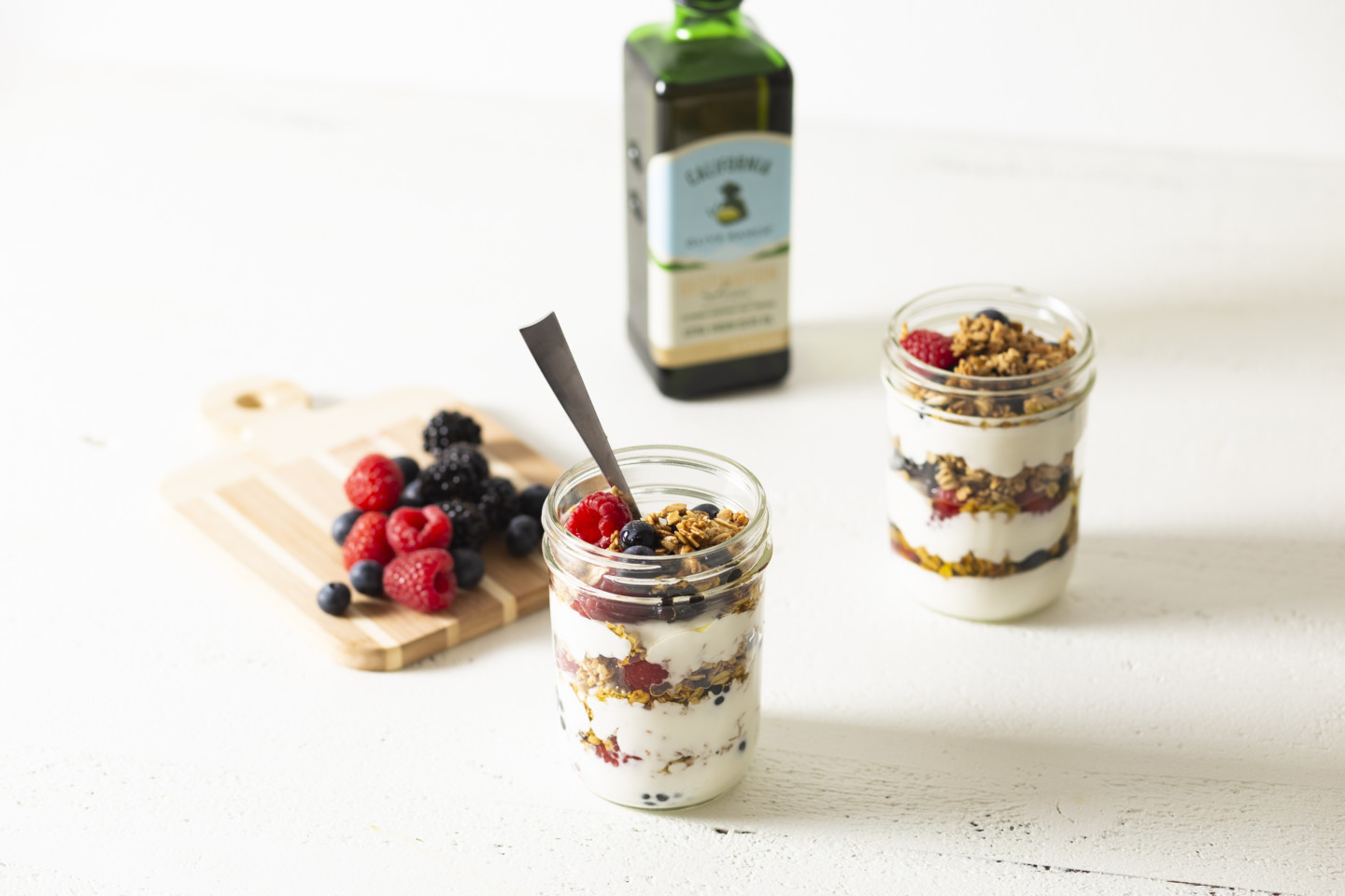 Two open jars of yogurt parfaits next to a bottle of California Olive Ranch Everyday Olive Oil and a chopping board with a selection of blueberries, raspberries, and blackberries.