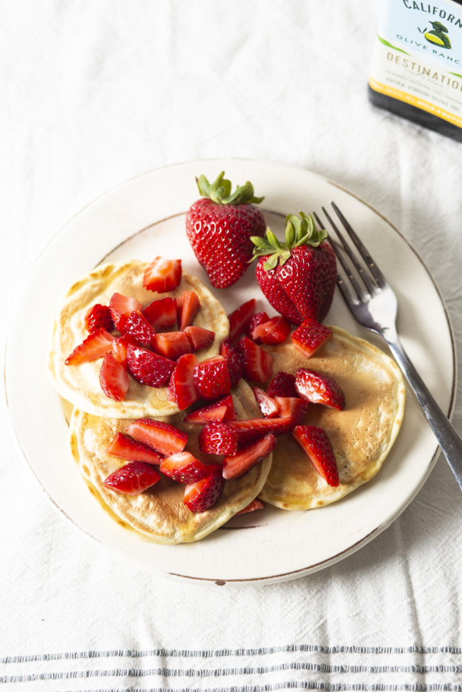 A plate of pancakes made with California Ranch Olive Oil that's been topped with plenty of fresh, chopped strawberries.