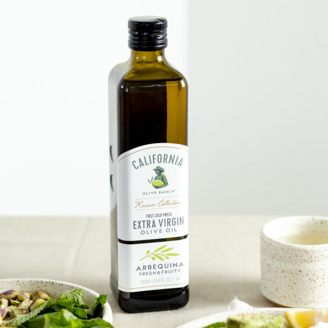 A bottle of California Olive Ranch Arbequina Extra Virgin Olive Oil sitting next to a dish of spring Panzanella salad.