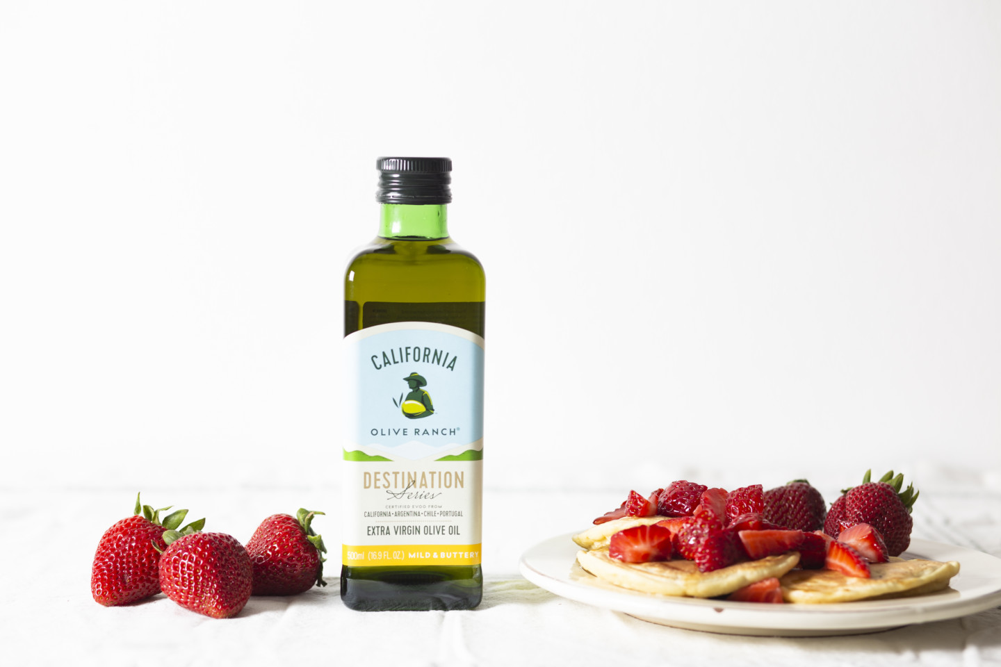 A bottle of California Olive Ranch Extra Virgin Olive Oil that's placed next to a plate of small pancakes with many strawberries on them.