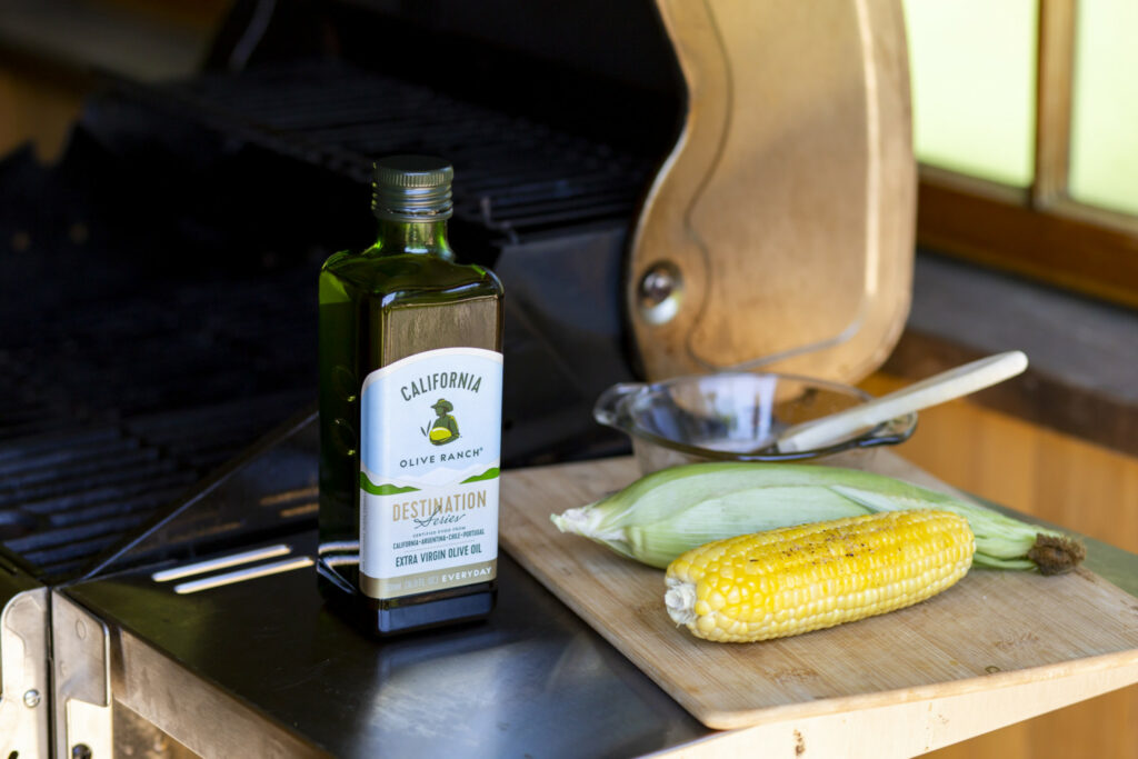 A bottle of California Olive Ranch Extra Virgin Olive Oil sitting on a countertop next to a cutting board with two cobs of corn.