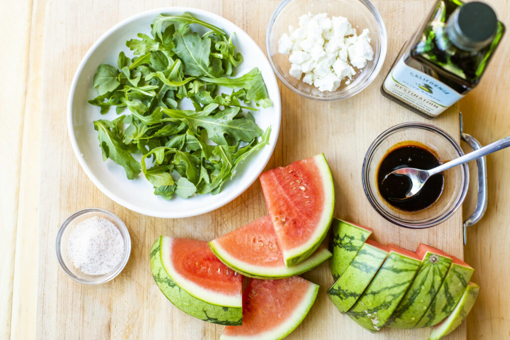 Half of a chopped, seedless watermelon, a bowl of baby arugula, a bottle of California Olive Ranch Everyday Extra Virgin Olive Oil, and various ingredients on a countertop.