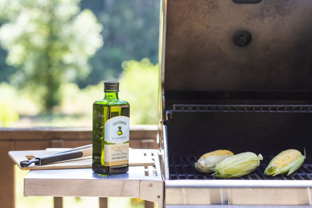 A bottle of California Olive Ranch Everyday Extra Virgin Olive Oil sitting next to a grill that has three cobs of corn on it.