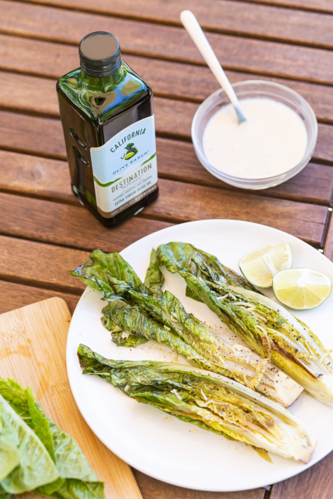 A plate with three pieces of grilled Caesar salad on it that's sitting alongside a bottle of California Olive Ranch EVOO.