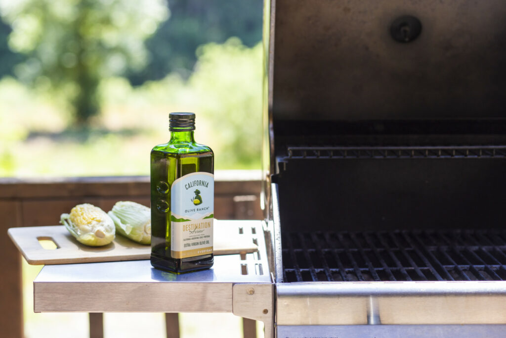 A bottle of California Olive Ranch Extra Virgin Olive Oil sitting on the side countertop of an open grill.