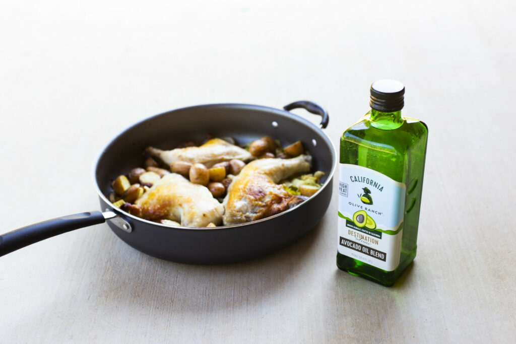 A skillet containing a few chicken thighs placed alongside a bottle of California Olive Ranch Avocado Oil Blend.