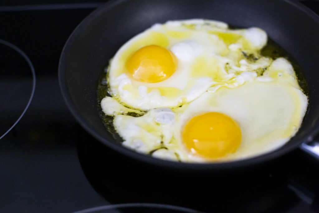 Two sunny side up eggs that are cooking in a frying pan.