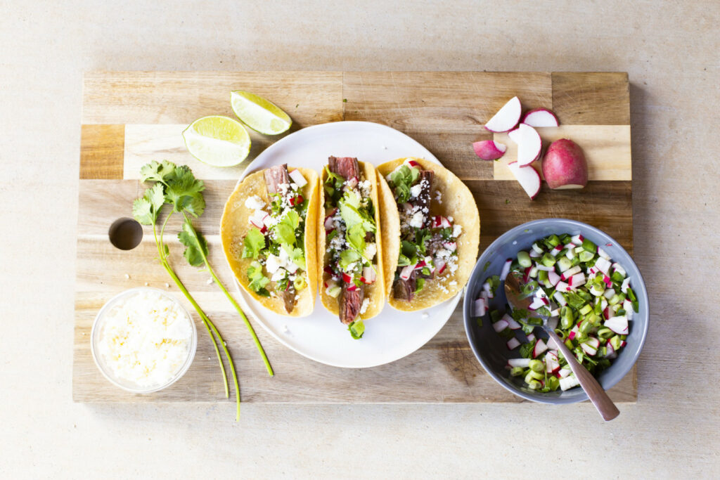 A plate with three steak tacos on it alongside a bowl of cilantro radish salsa and various cooking ingredients.
