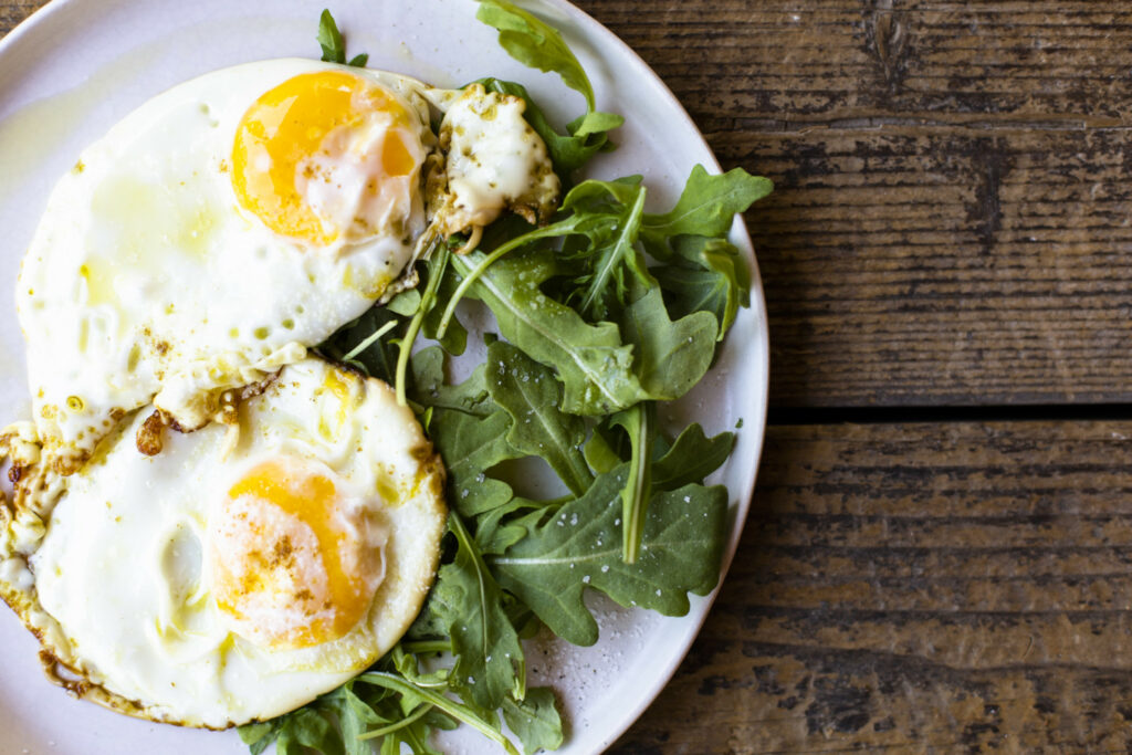 A plate with two sunny side up eggs and some arugula that's sitting on a wooden countertop.