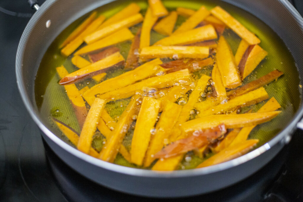 Many French fries being cooked in a pan full of extra virgin olive oil.