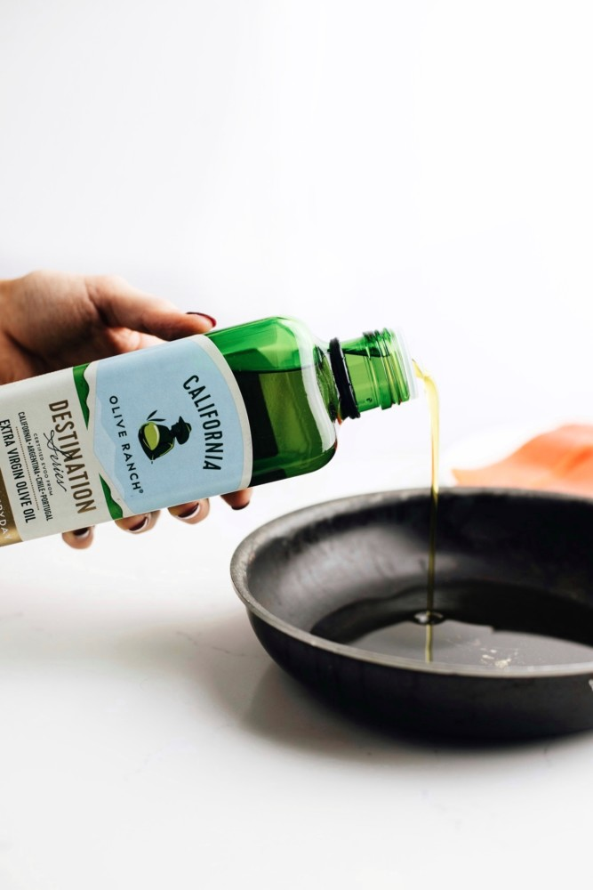 Extra virgin olive oil being poured into a pan