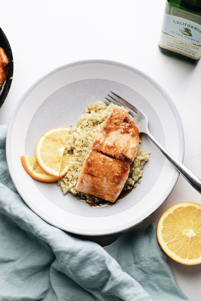 Citrus glazed salmon over rice next to a bottle of olive oil
