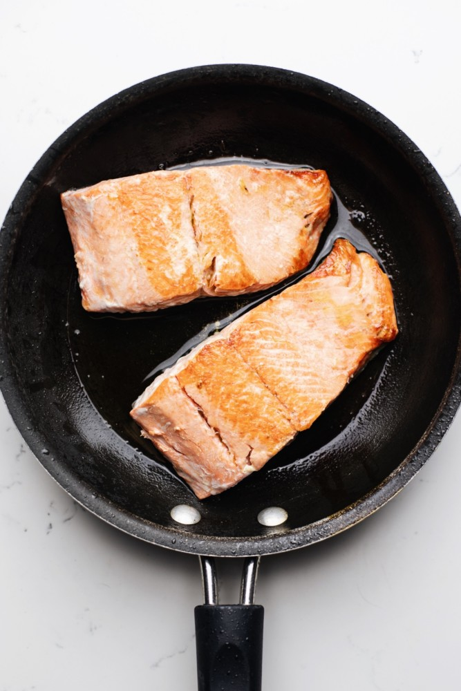 Citrus glazed salmon in a frying pan