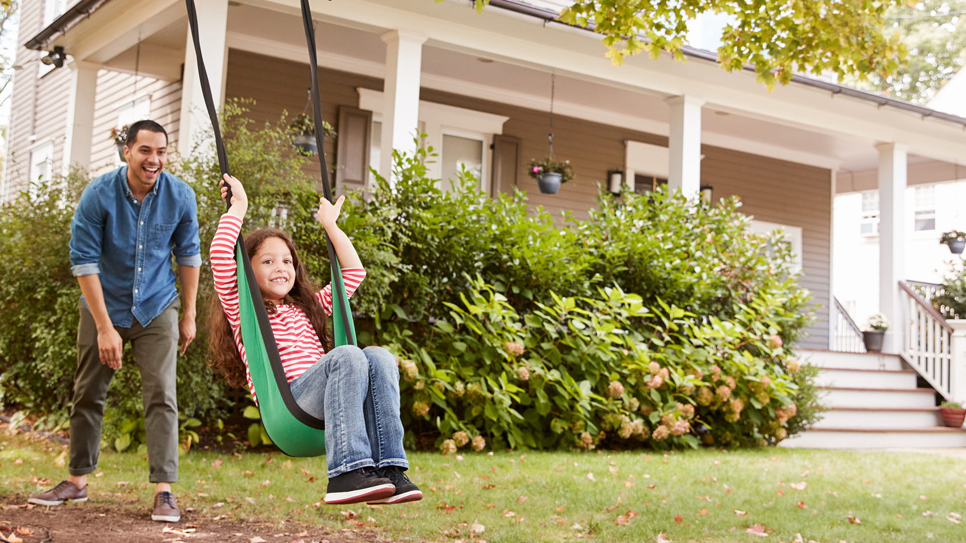 Father pushing daughter on swing in yard.