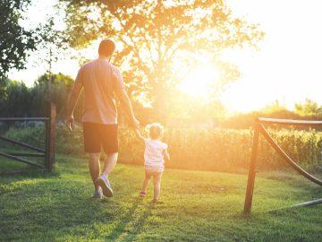 Man and daughter walk around field during sunset