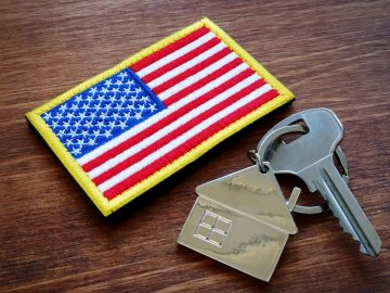 A house key lies on a table next to a military patch shaped like an American flag.