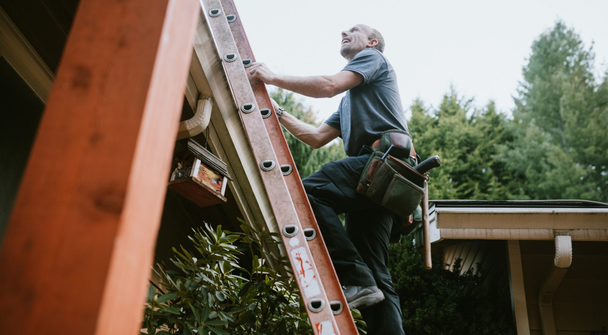 A man climbs a ladder to his home's roof