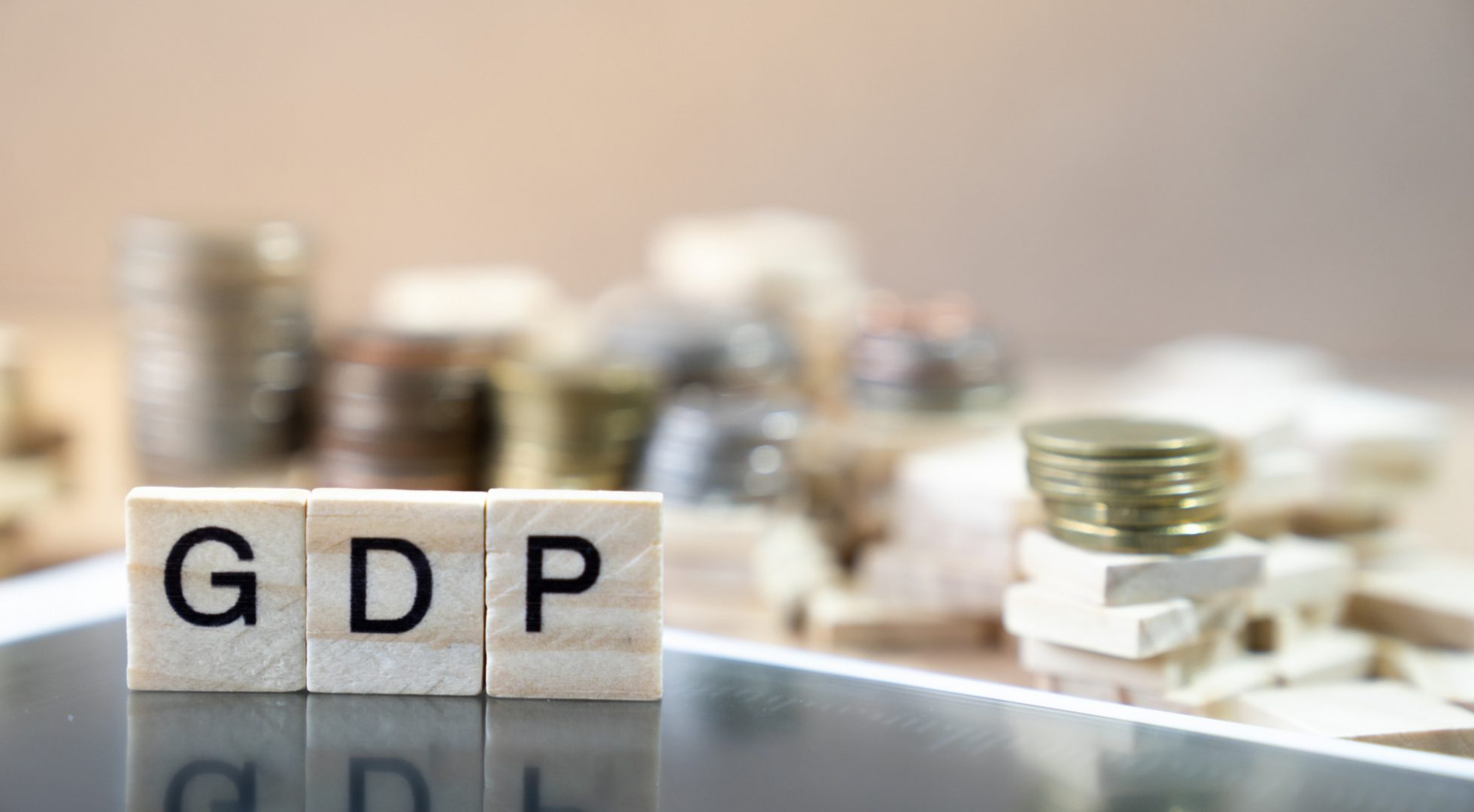 """""""GDP"""" spelled out with Scrabble tiles on desk."""