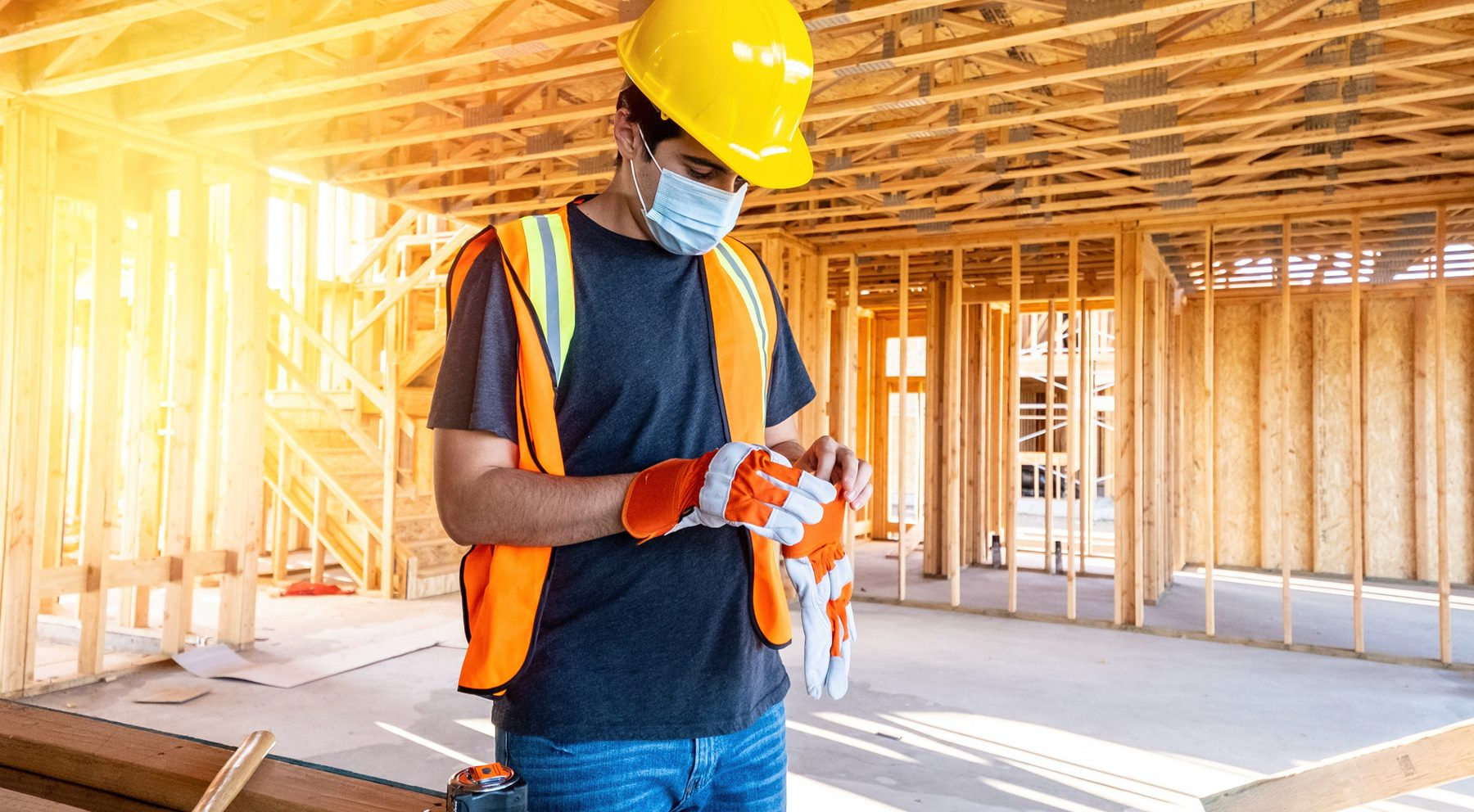 Young male construction worker wearing a protective face mask.