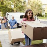 An excited family moves boxes into their new home.
