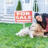 A woman pets her dog in front of home she has listed for sale.
